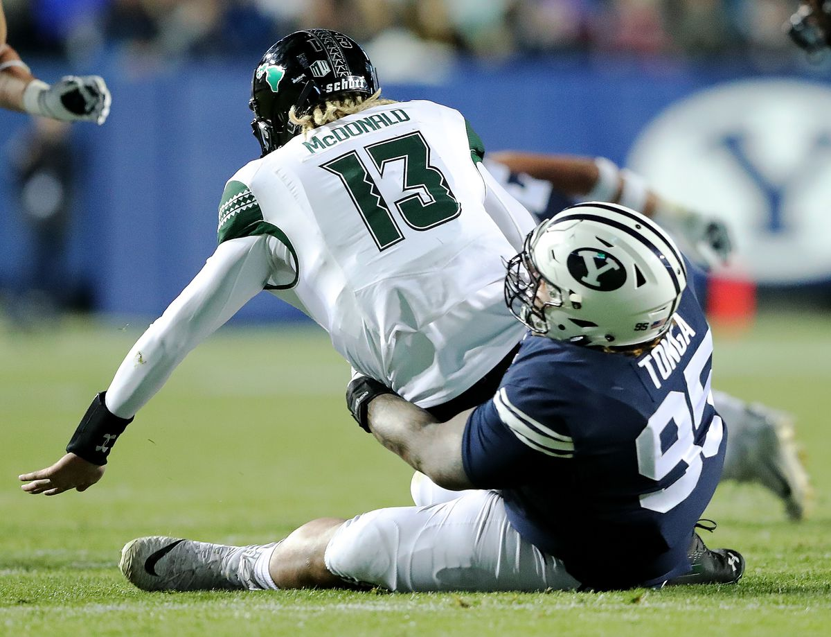 Hawaii Warriors quarterback Cole McDonald is sacked by BYU defensive lineman Khyiris Tonga (95) as BYU and Hawaii play at LaVell Edwards Stadium in Provo on Saturday, Oct. 13, 2018.