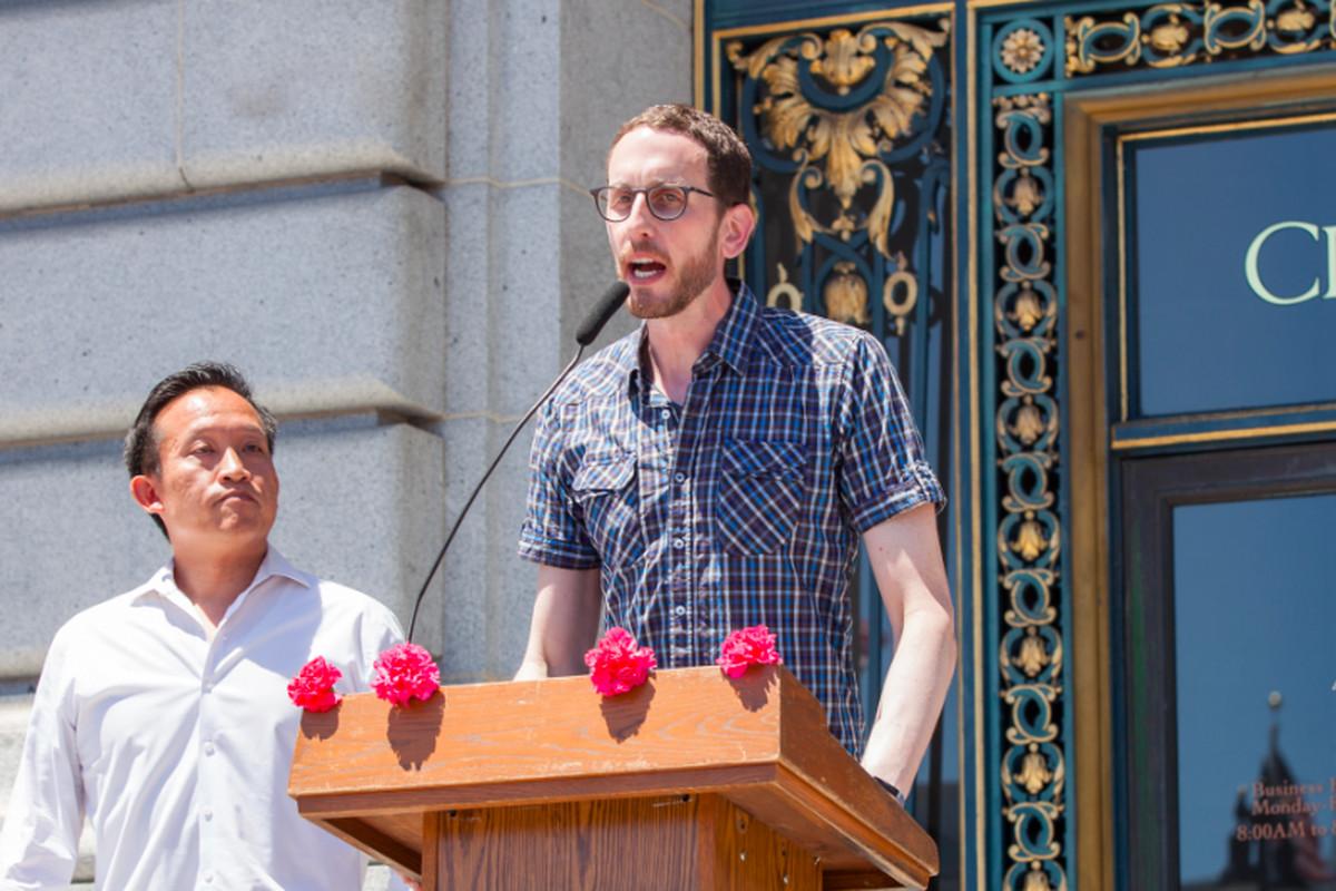 Senator Scott Wiener speaking at a podium on the steps of SF City Hall.
