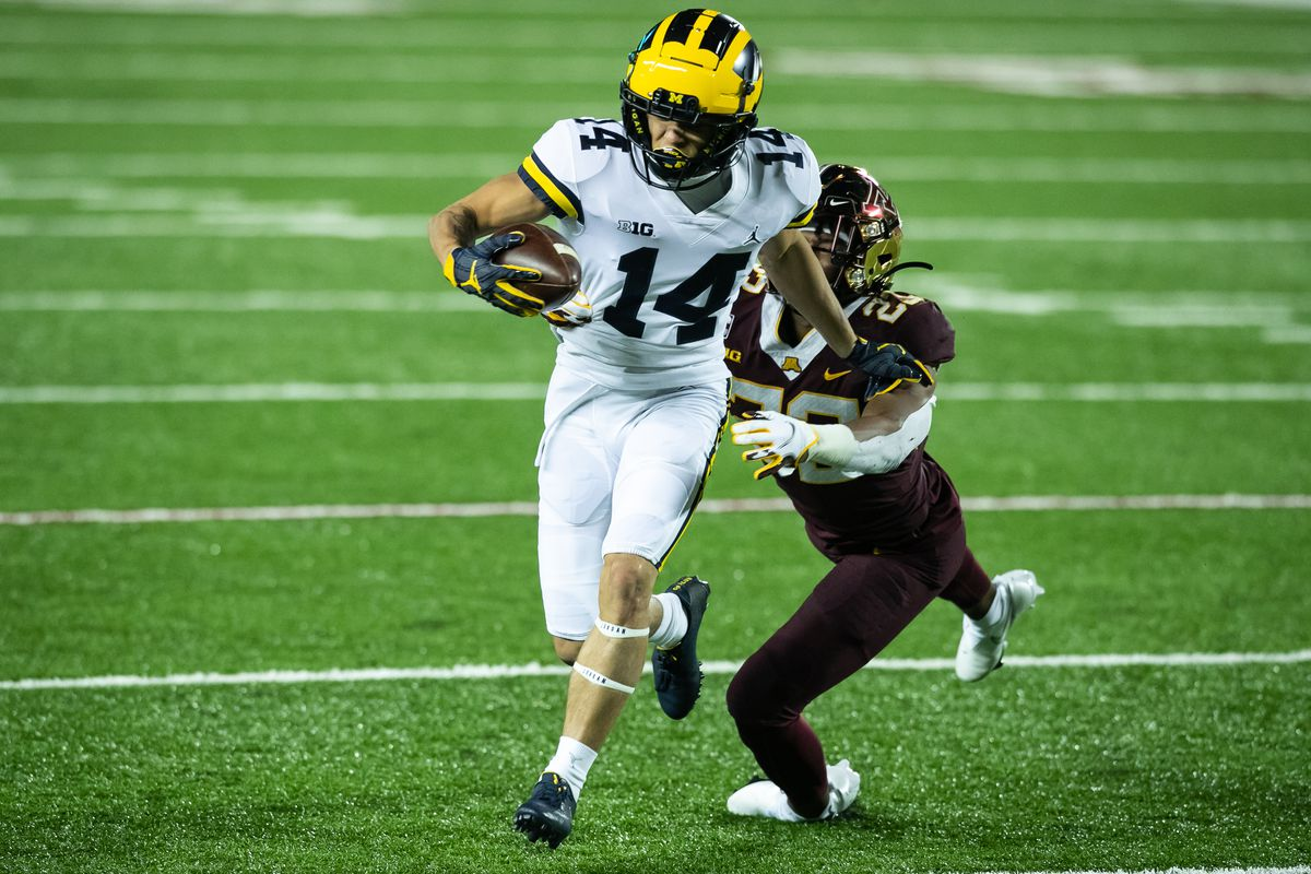 Roman Wilson of the Michigan Wolverines carries the ball past Jordan Howden of the Minnesota Golden Gophers in the third quarter of the game at TCF Bank Stadium on October 24, 2020 in Minneapolis, Minnesota. The Wolverines defeated the Gophers 49-24.