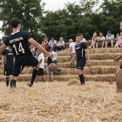 """In this photo taken on Saturday, June 4, 2016, people ply football at the arena, made of 4,500 straw bales, comes complete with tiered seating and flagpoles in Krasnoye, Stavropol region, South Russia. In a project straight out of the """"Three Little Pigs"""" fairytale, Roman Ponomarev has built a straw replica of the 643-billion-ruble ($700 million) stadium in St. Petersburg which will host World Cup semifinals. (AP Photo/Oleksandr Stashevskyi) ORG XMIT: XAZ126"""
