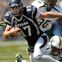 Nevada quarterback Cody Fajardo (17) runs from South Florida defenders Sam Barrington (36) and Mark Joyce (26) during the first half of an NCAA college football game Saturday, Sept. 8, 2012, in Reno, Nev.