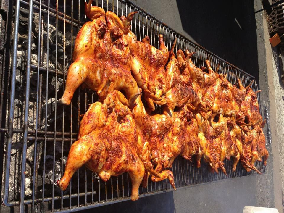 A length of whole chickens rubbed in an anchitoe marinade are lined up on a charcoal grill outside