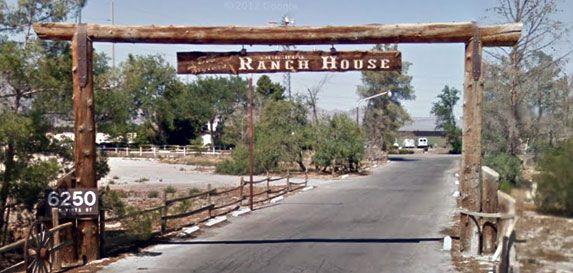 A ranch sign with a driveway in between