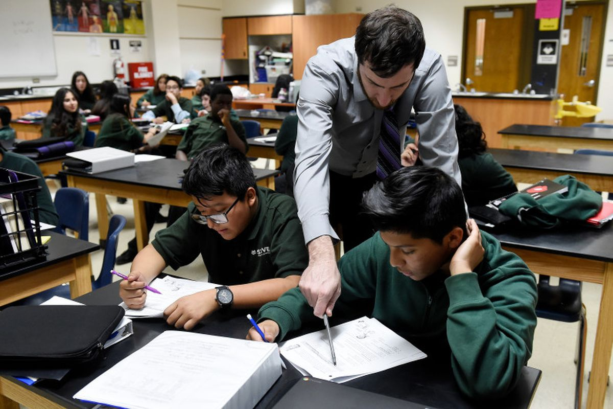 Justin Walker helps STRIVE Prep – Montbello students work through a problem during a seventh-grade biology class on January 30, 2017.