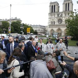 """French interior minister, Gerard Collomb, center left, addresses the media after a man attacked police officers with a hammer on the esplanade of the Notre Dame cathedral in Paris, France, Tuesday, June 6, 2017. Gerard Collomb says the attacker cried """"it's for Syria"""" as he went after officers patrolling an esplanade in front of the famous landmark."""