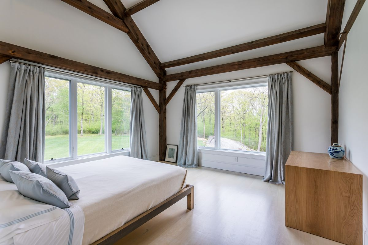 A bedroom with white bed, exposed wood, and windows.