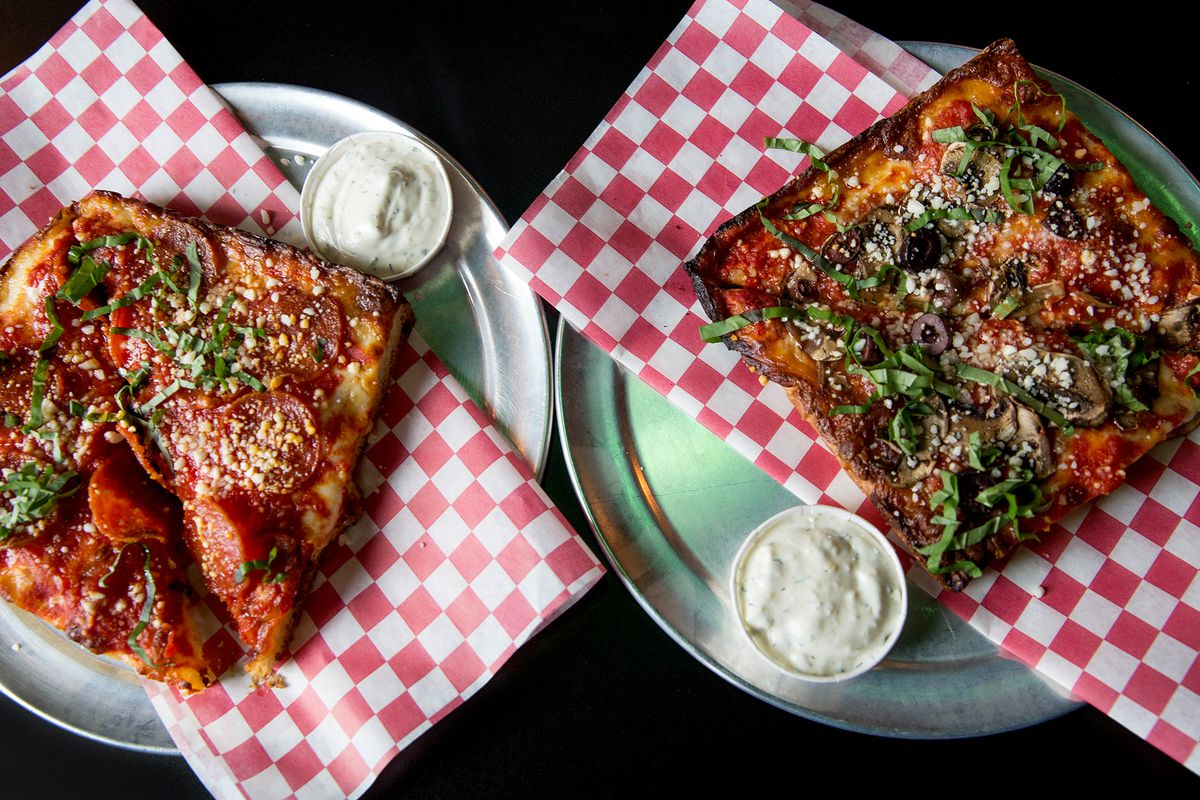 Two squares of Ranch Pizza sit on plates at the now-closed Poison's Rainbow