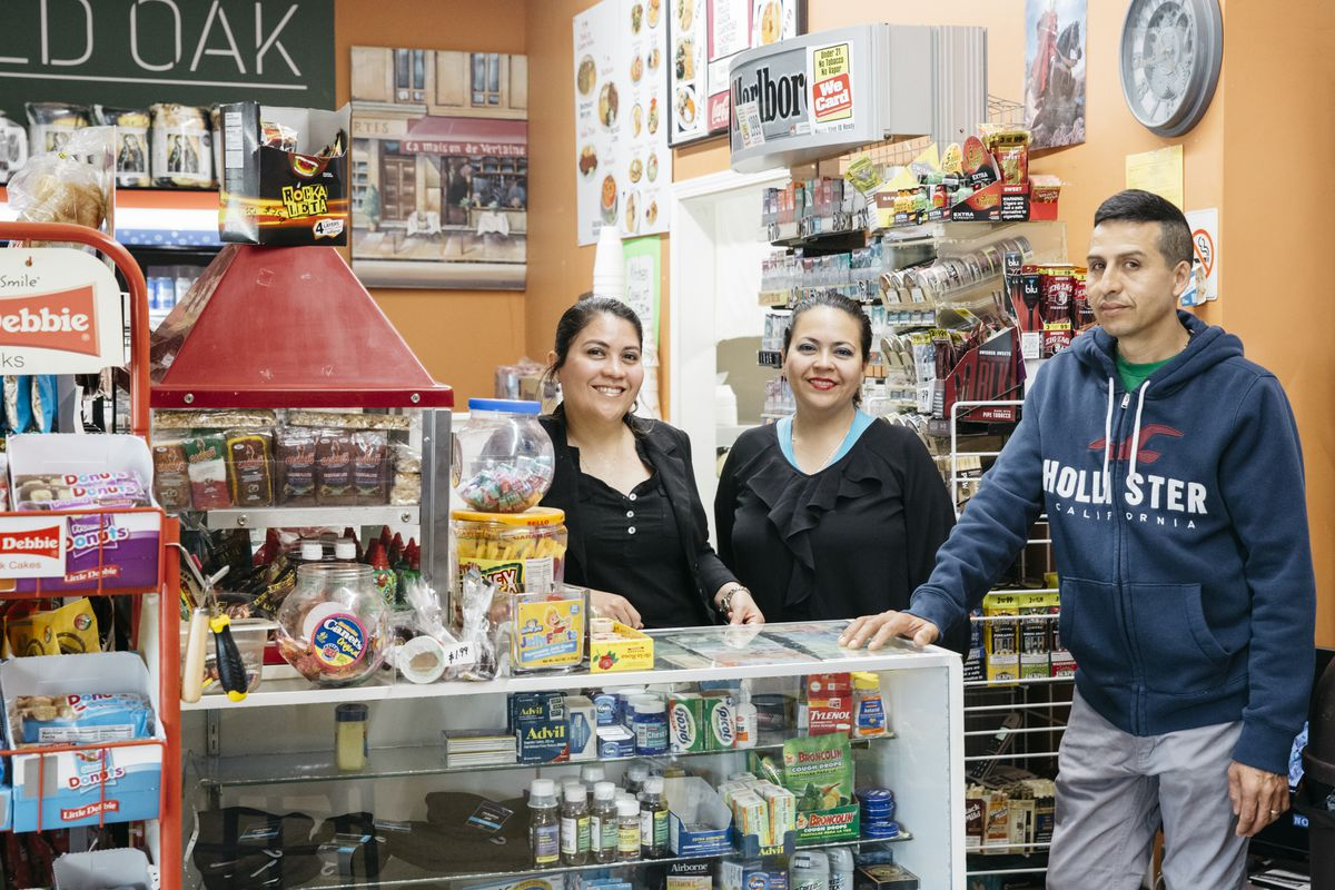 Two women smiling from behind a convenience store counter next to a man smiling in front of it.