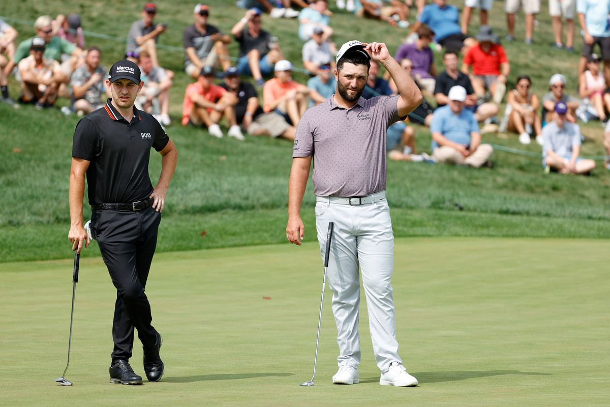 Patrick Cantlay of the United States and Jon Rahm of Spain look on over the ninth green while playing with Bryson DeChambeau of the United States during the third round of the BMW Championship at Caves Valley Golf Club on August 28, 2021 in Owings Mills, Maryland.