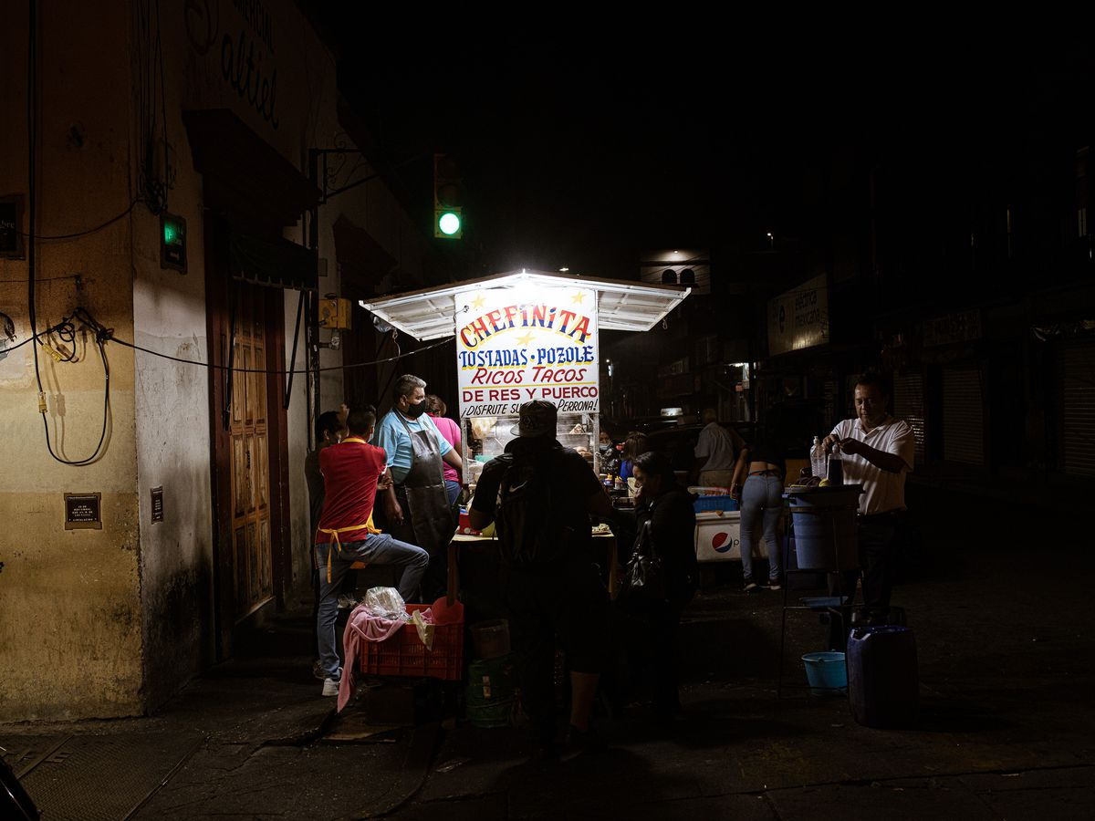 An illuminated street cart is surrounded by people at night.