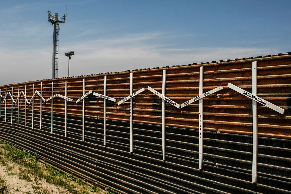 A border fence in Tijuana, with white crosses nailed to it.