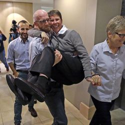 Plaintiffs, from left, Moudi Sbeity, his partner Derek Kitchen, Kody Partridge and her wife, Laurie Wood, celebrate following a news conference Monday, Oct. 6, 2014, in Salt Lake City. The U.S. Supreme Court on Monday rejected an appeal from Utah and four other states that had sought to bar weddings between gay couples.