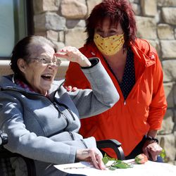 Staff member Vicki McRae reacts with Elna Berlin as Berlin's family drives past residents at The Ridge Cottonwood senior living center in Holladay during a Mother's Day parade on Saturday, May 9, 2020.
