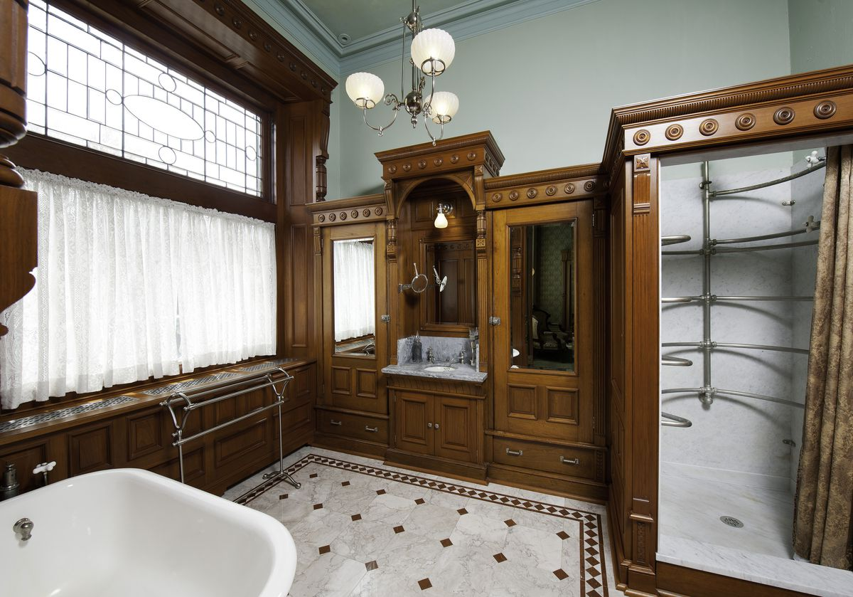 A bathroom has built-in wood cabinets and an old-fashioned sink. There is a shower and white tub.