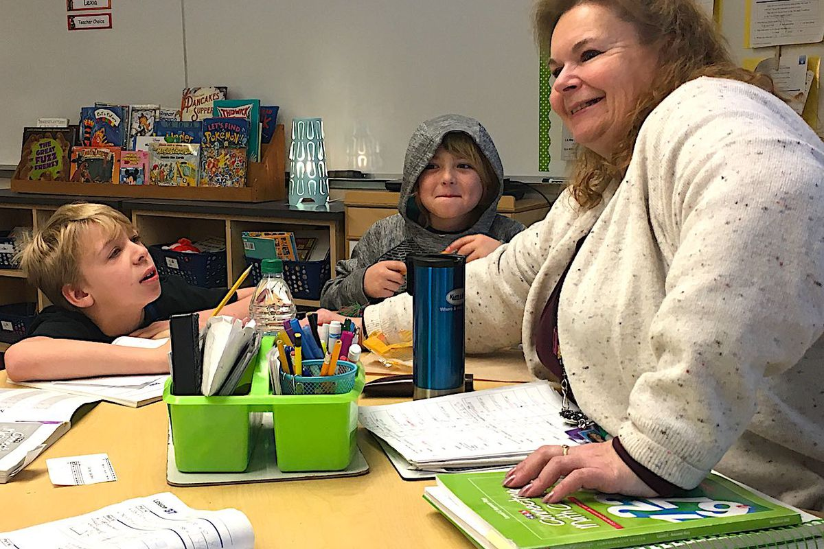 Wendy McSwain, a paraprofessional at Heiman  Elementary School in Evans, works with two students in a math group.