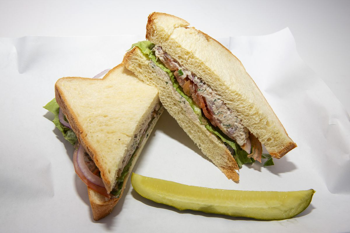 A sandwich laid out on white deli paper with a pickle spear