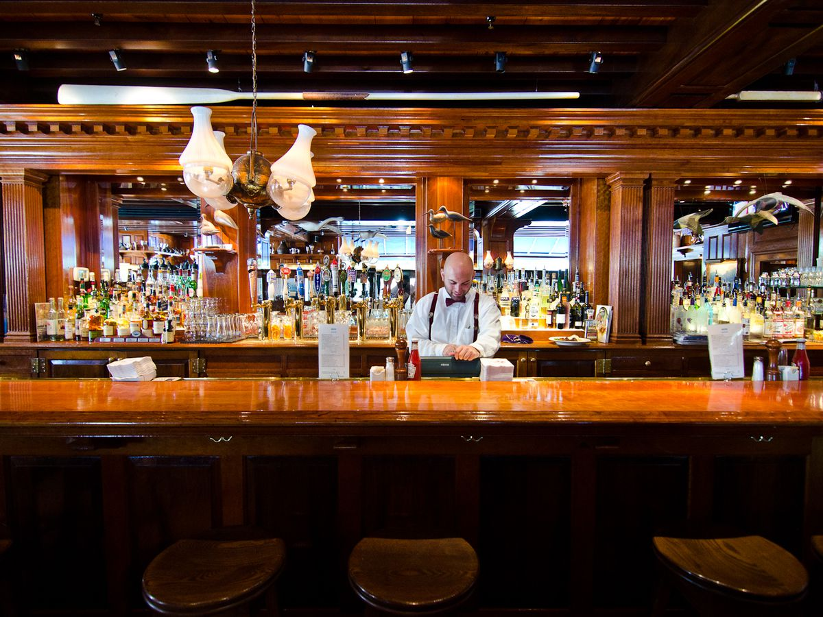 The wooden bar, with a bartender in suspenders