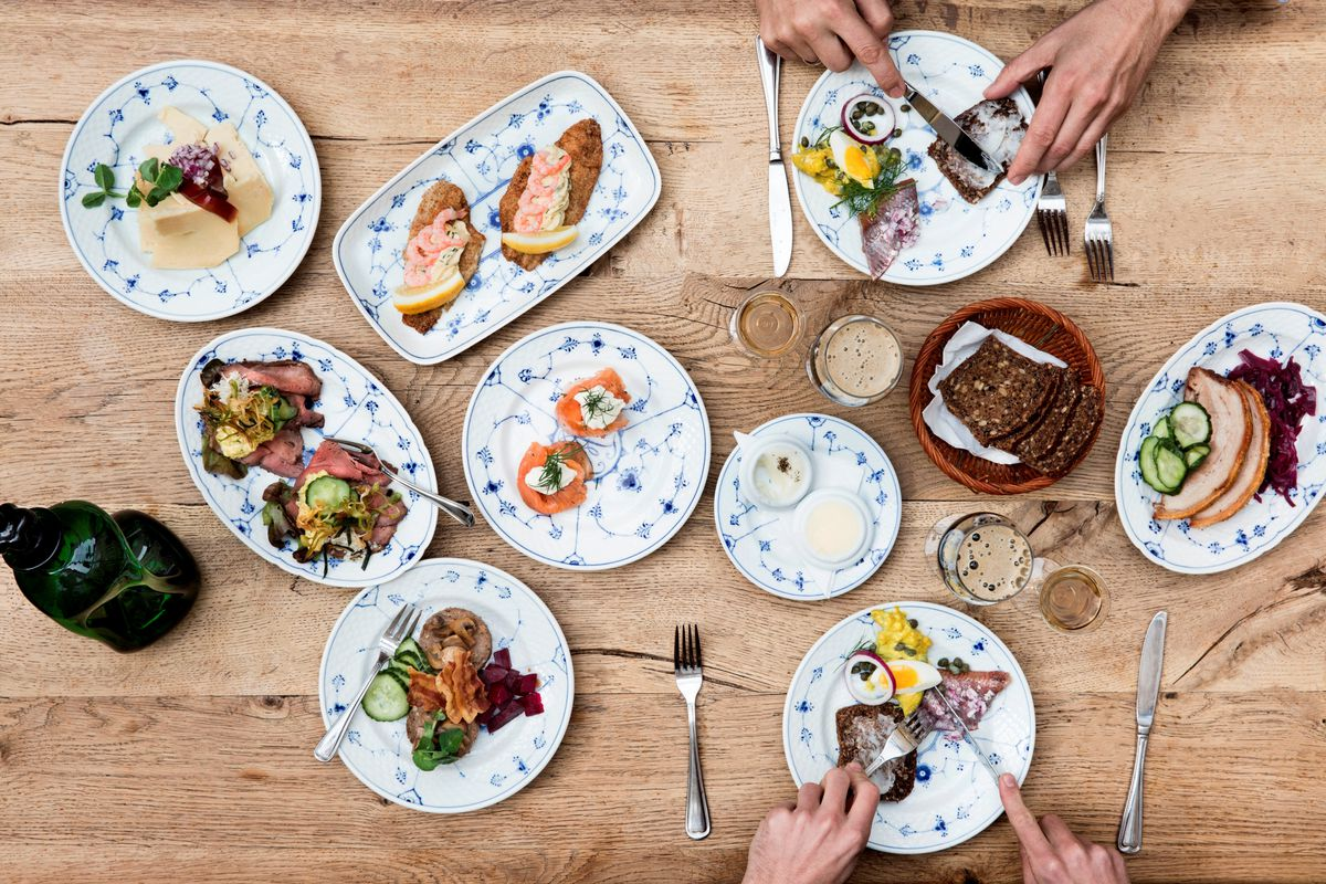 A top-down shot of a wooden table filled with small toppings for sandwiches including smoked fishes, pickled vegetables, cold cuts, and spreads, all displayed on decorative, floral ceramic dishes.