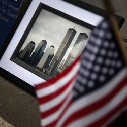 A framed photo of the Twin Towers is sits against a curb in honor of a 9/11 victim near Ground Zero during the 10th anniversary ceremony, Sunday, Sept. 11, 2011, in New York.