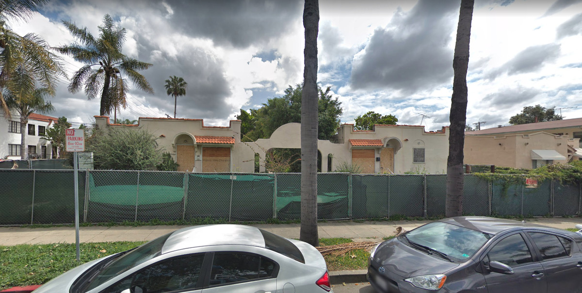 A photo of the bunglow court now that shows it surrounded by a green chainlink fence. The windows and doors are boarded up. The units are empty.