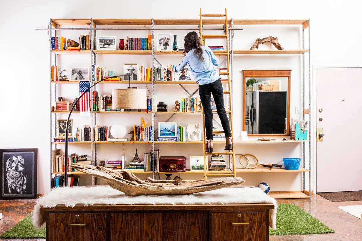 A woman stands on a ladder bookshelf.