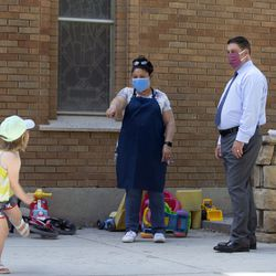 Preschool teacher Ana Jerez-Flores, center, and the Rev. Curtis Price, right, watch Evalynn, left, dance as day care children play outside of the First Baptist Church in Salt Lake City on Wednesday, June 24, 2020. The Trump administration sparked an outcry this spring by allowing churches to apply for COVID-19 relief funds set aside for small businesses. The Rev. Price, who applied for and received between $150,000 and $200,000 in small-business stimulus funds for his church, said the program accomplished its goal, at least in his case. Thanks to the paycheck protection loan, First Baptist Church avoided laying off any of its 40 employees.