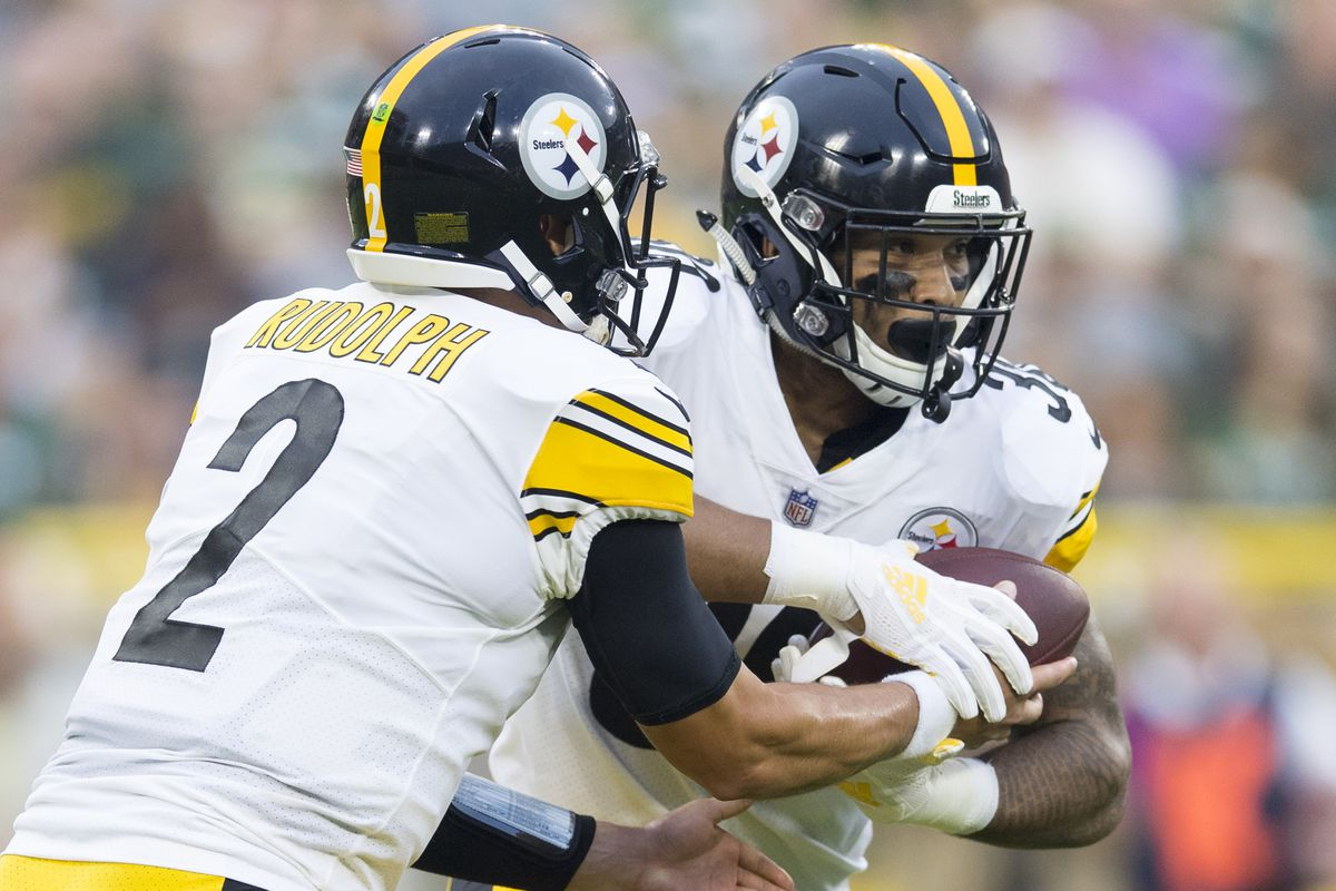 Pittsburgh Steelers quarterback Mason Rudolph hands the football off to running back James Conner during the first quarter against the Green Bay Packers at Lambeau Field.