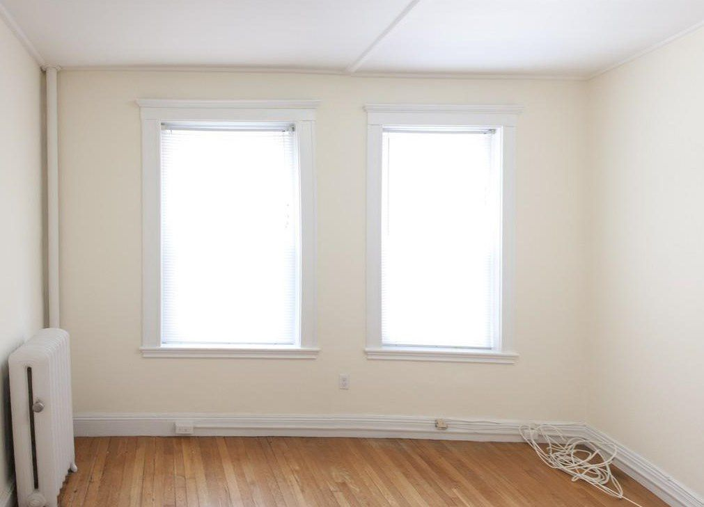 An empty room with two windows and a radiator.