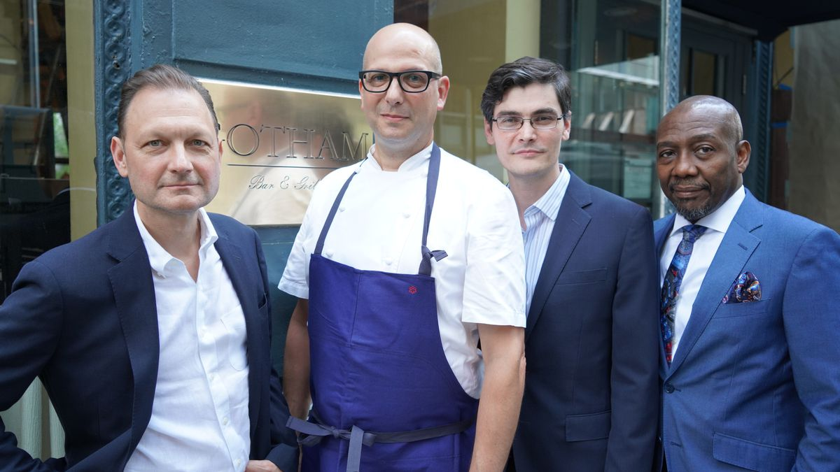 """Three men in suits and one man in a white chefs coat and a blue apron stand outdoors in front of a gold-plated restaurant sign reading """"Gotham"""""""