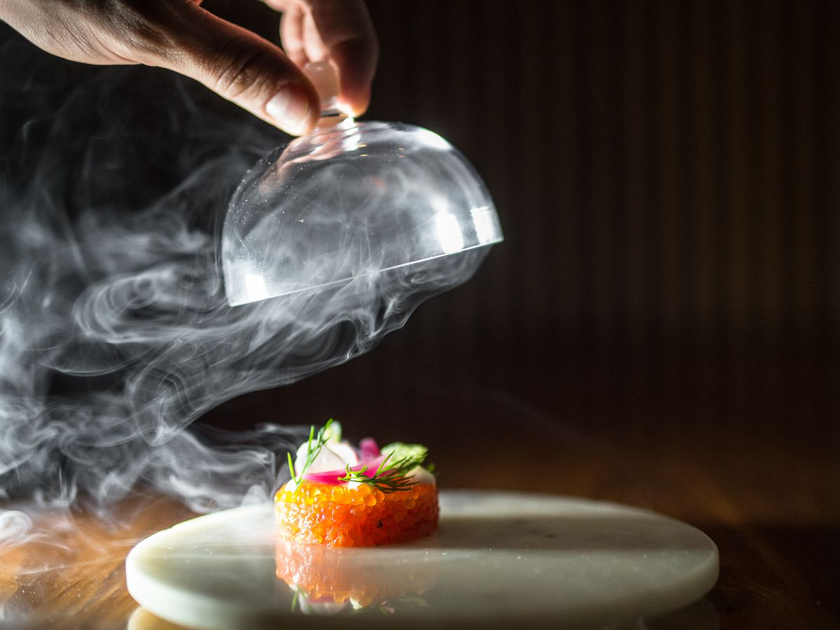 Aquavit's orange salmon tartare is surrounded by a cloak of smoke as a waiter removes a cloche.