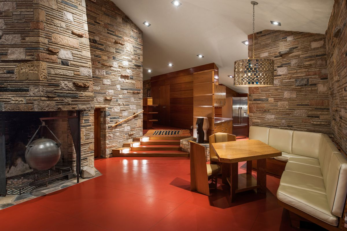 A dining room has a large stone fireplace, built-in white leather bench, and a geometric dining table.
