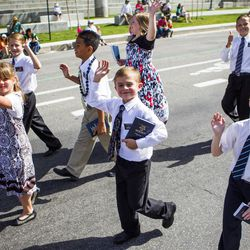 Kids wave as they walk behind the Bennion Utah West Stake float during the Days of '47 Union Pacific Railroad Youth Parade held Saturday, July 18, 2015, in Salt Lake City.