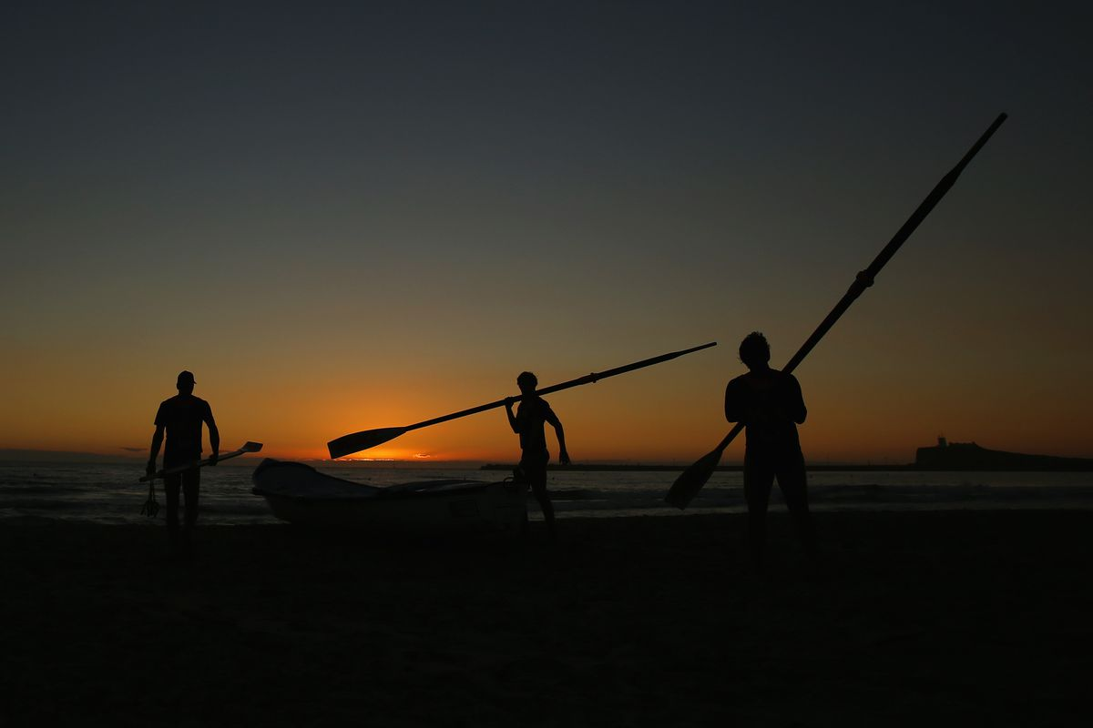 A surf boat crew prepare their boat for competition as the sun rises during the Australian Surf Rowers League Open Championships at Stockton beach on February 8, 2014 in Newcastle, Australia.
