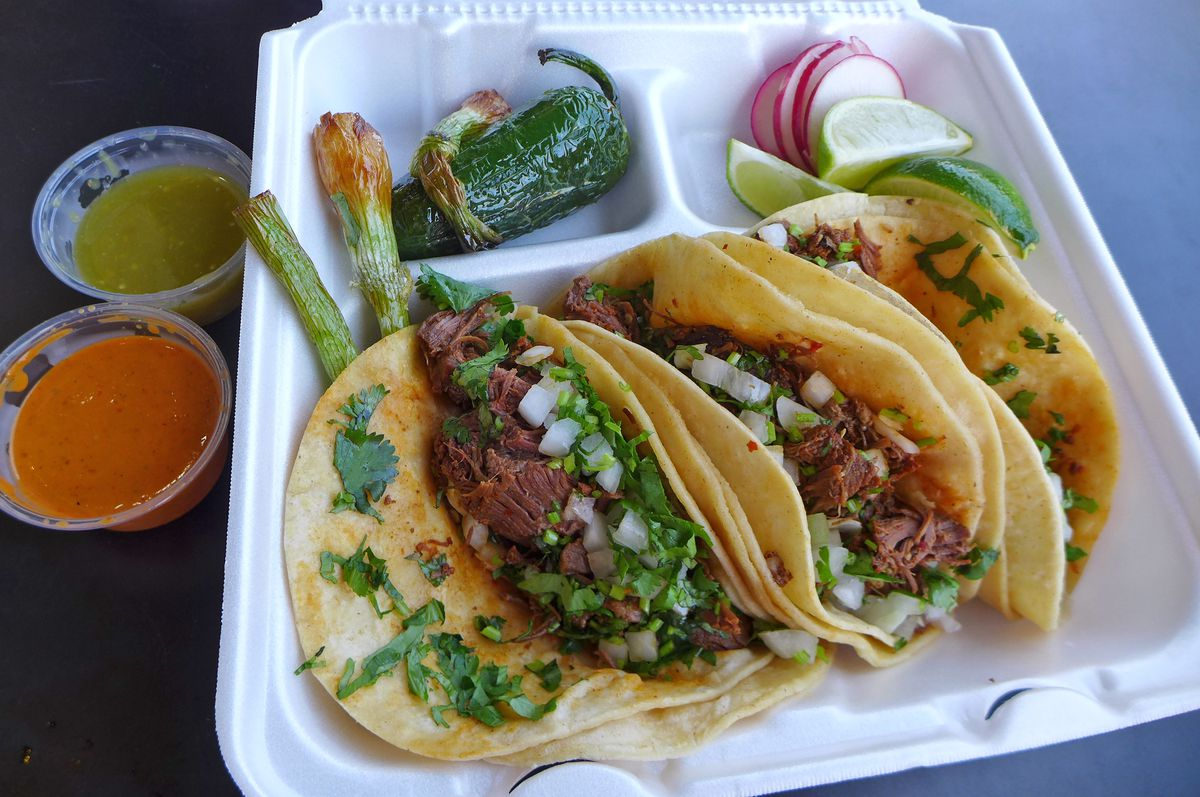 Three soft corn tacos filled with chunks of dark meat, with two green onions and one jalapeno on the side.