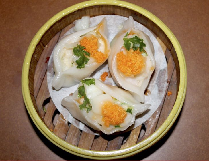 A container with three dumplings garnished with parsley