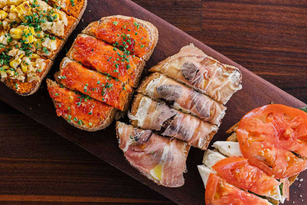 a wooden board on a table with four types of bruschetta