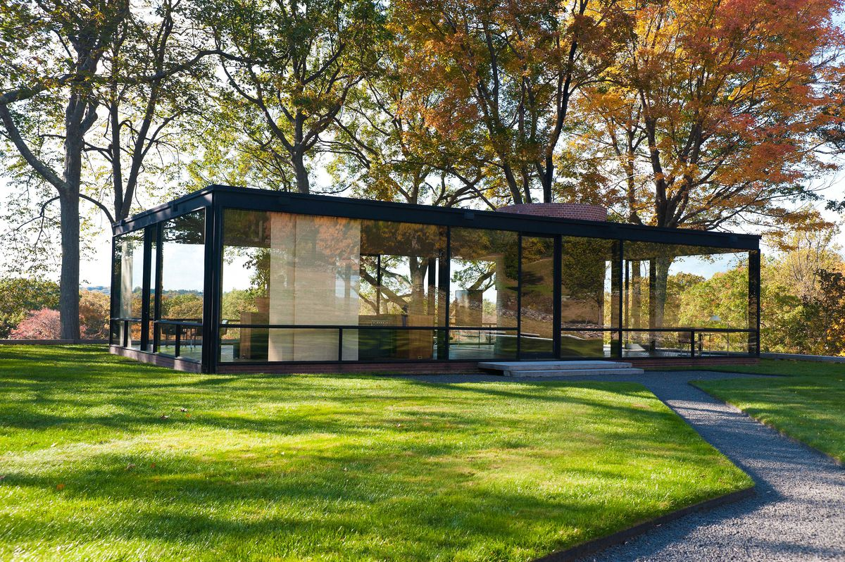 The exterior of Philip Johnson's Glass House in Connecticut. The roof is flat and the walls are glass. The building is surrounded by grass and trees.