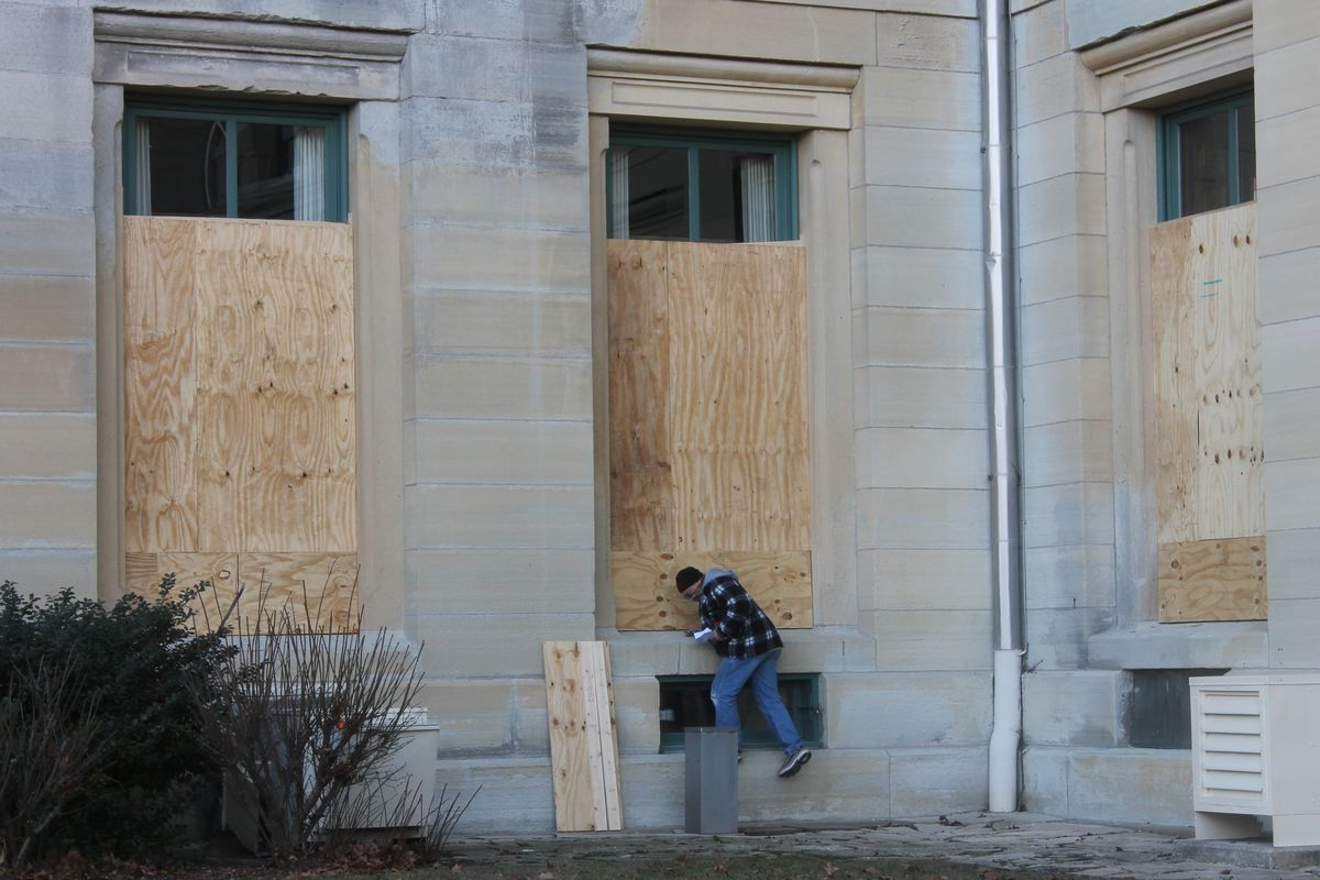 A worker removes sheets of plywood from windows at the Illinois State Capitol on Thursday.