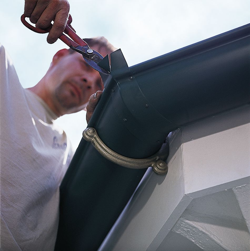 Man Cutting Section of Strip Miter With Snips For Rain Gutter