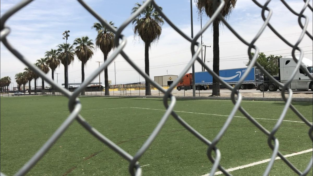An Amazon Prime truck drives into the BNSF rail yard. The rail yard sits across the street from a soccer field and community center in San Bernardino, California and attracts a steady stream of truck traffic.