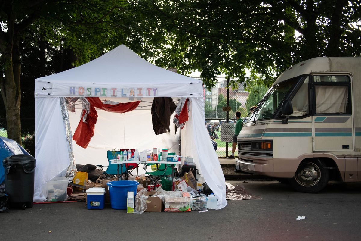 A makeshift hospitality tent near an RV around Cal Anderson Park