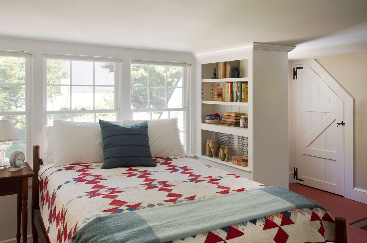 A country style bedroom that includes a bookcase with shiplap backing.