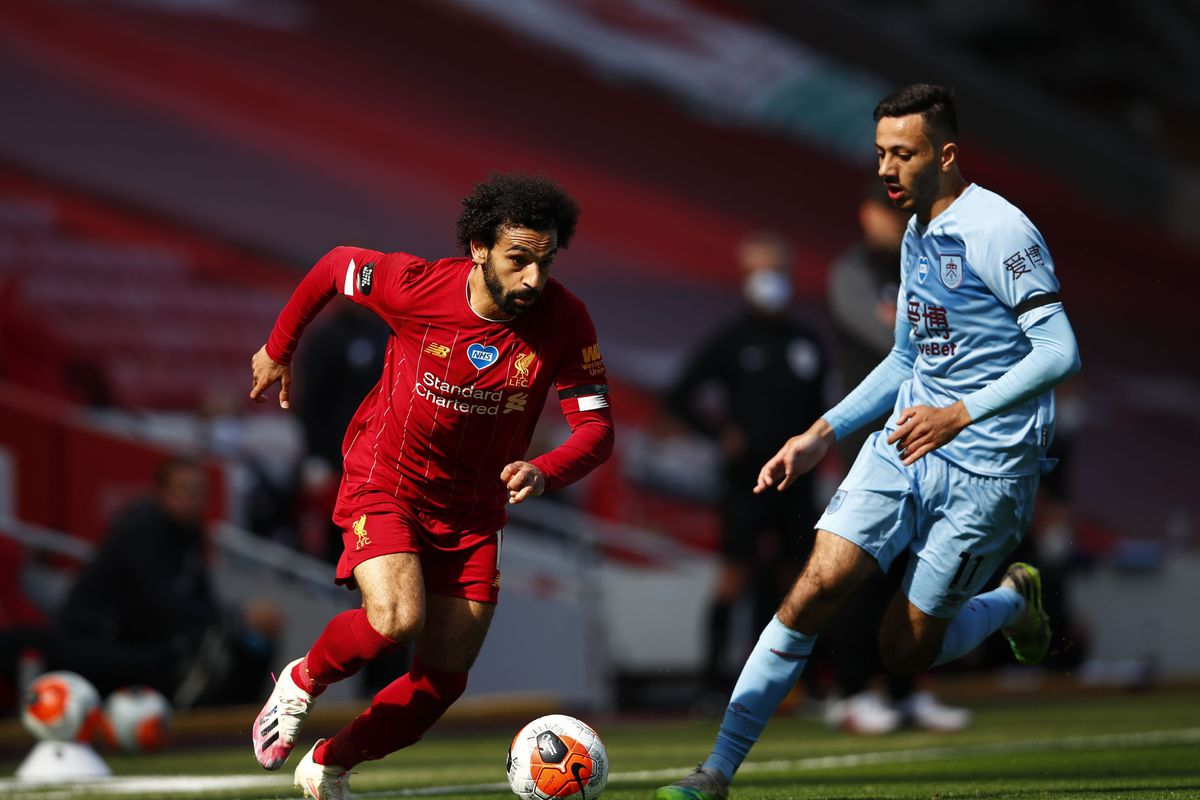 Mohamed Salah of Liverpool battles for possession with Dwight McNeil of Burnley during the Premier League match between Liverpool FC and Burnley FC at Anfield on July 11.