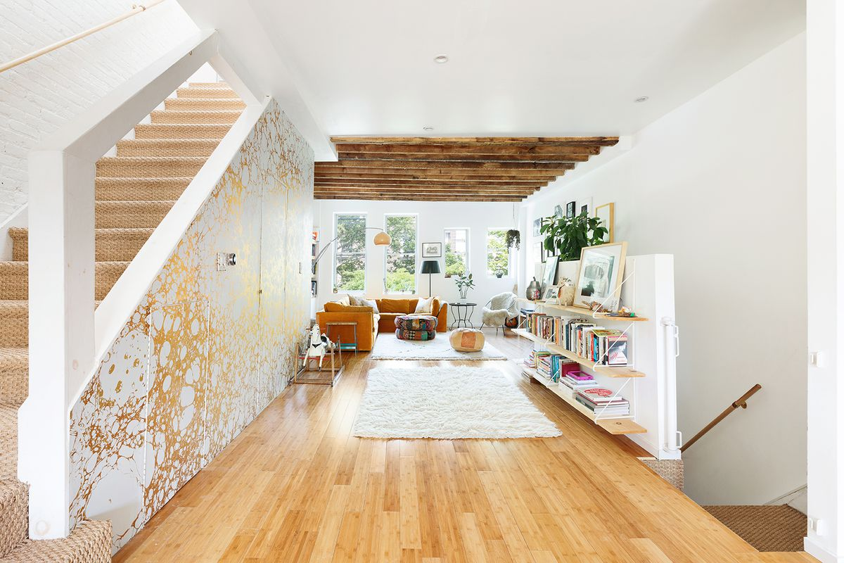 A foyer with hardwood floors, a staircase, a beige rug, and gold-foil wallpaper in one of its walls.