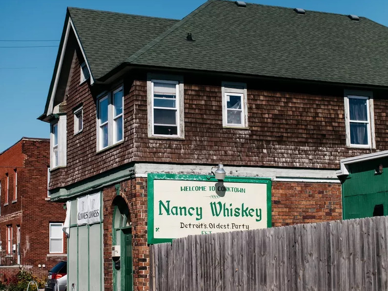 The green and white sign for Nancy Whiskey hangs on the side of the Victorian-style building with cedar shake and brick walls.