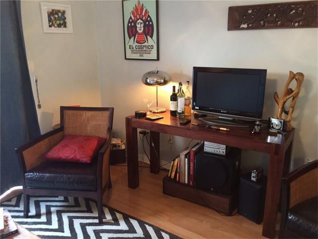 condo living room withbeige walls, vintage armchair, TV stand