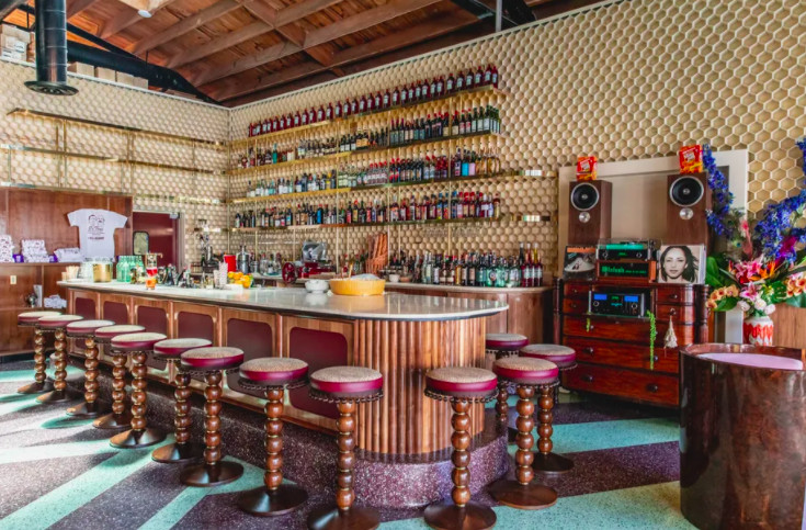 A central bar surrounded by bar stools with bottles on shelves in the background.