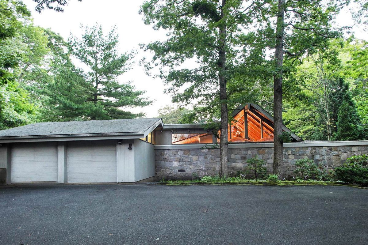 Shot of grey home with two car garage and peaked roof with low stone wall running in front of it.