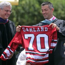 Niles West Principal Jason Ness, right, presents a Niles West hockey jersey to Supreme Court nominee.   Tim Boyle/For the Sun-Times