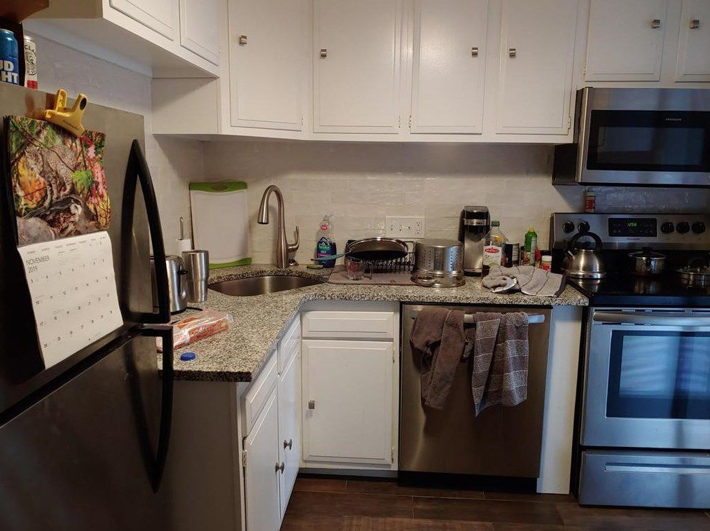 A small kitchen with two counters meeting at a right angle.